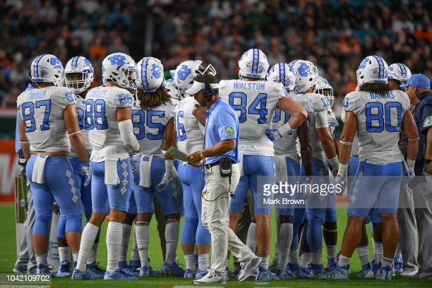 Head coach Larry Fedora of the North Carolina Tar Heels walks by his players during a break in the first quarter against the Miami Hurricanes at Hard...