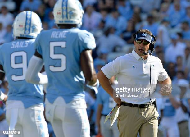 Head coach Larry Fedora talks to KJ Sails and Patrice Rene of the North Carolina Tar Heels during their game against the Virginia Cavaliers at Kenan...