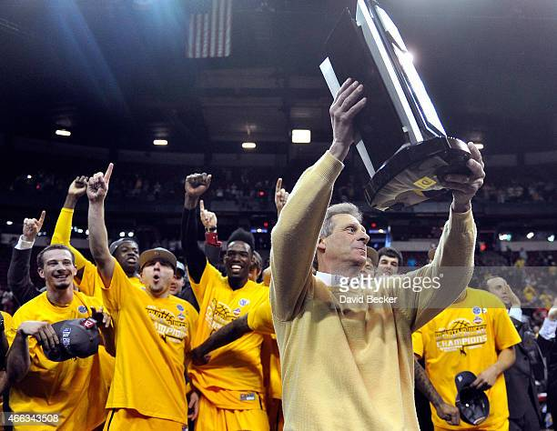 Head coach Larry Shyatt of the Wyoming Cowboys holds the championship trophy after defeating the San Diego State Aztecs during the championship game...