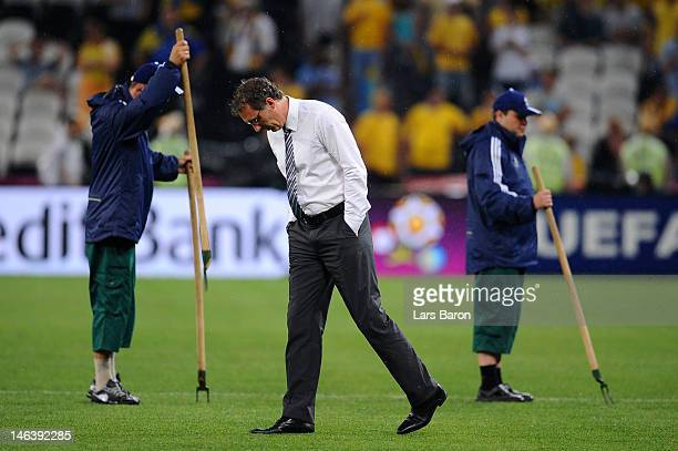 Head Coach Laurent Blanc of France looks on as groundsman attend to the waterlogged pitch during the UEFA EURO 2012 group D match between Ukraine and...