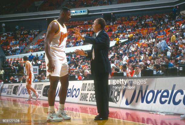 Head coach Lenny Wilkens of the Atlanta Hawks talks with his player Andrew Lang during an NBA basketball game circa 1994 at the Omni Coliseum in...