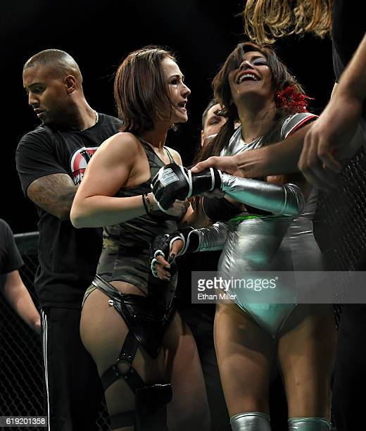 Head coach Leon Hater and Lingerie Fighting Championships President Maxine Frost help remove fighter Shelly Aphrodite DaSilva from the cage after she...