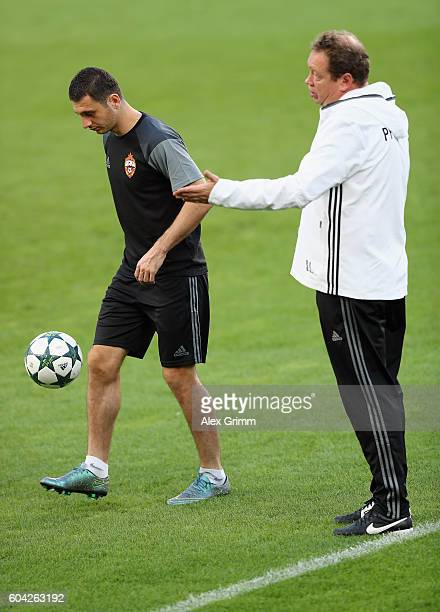 Head coach Leonid Slutski walks past Alan Dzagoev during a CSKA Moskva training session ahead of their UEFA Champions League Group E match against...