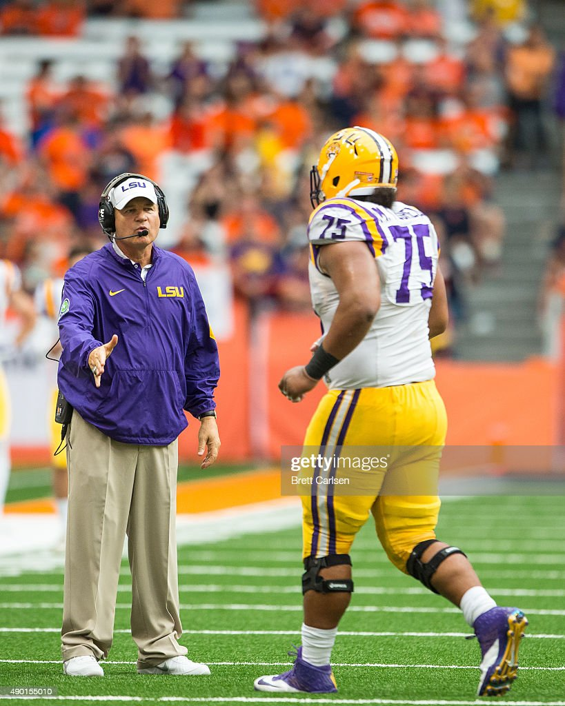 Head coach Les Miles of the LSU Tigers congratulates Maea Teuhema #75 of the LSU Tigers after a play against the Syracuse Orange on September 26, 2015 at The Carrier Dome in Syracuse, New York. LSU defeats Syracuse 34-24.