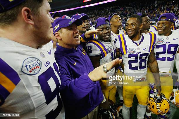 Head coach Les Miles of the LSU Tigers sings with his team after they defeated the Texas Tech Red Raiders 5627 during the AdvoCare V100 Texas Bowl at...