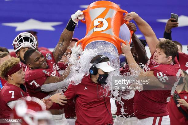 Head coach Lincoln Riley of the Oklahoma Sooners is doused with water in the final seconds of the Sooners 55-20 win against the Florida Gators at...