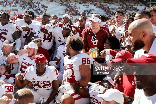 Head coach Lincoln Riley of the Oklahoma Sooners poses with the team for a photo with the trophy after the game against the Texas Longhorns during...