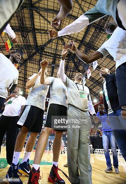 Head Coach Lionel Hollins of Team World smiles during a huddle after practice for the NBA Africa Game 2015 as part of Basketball Without Borders on...