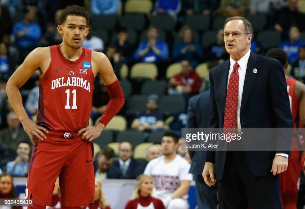 Head coach Lon Kruger of the Oklahoma Sooners speaks to Trae Young in the first half of the game against the Rhode Island Rams during the first round...