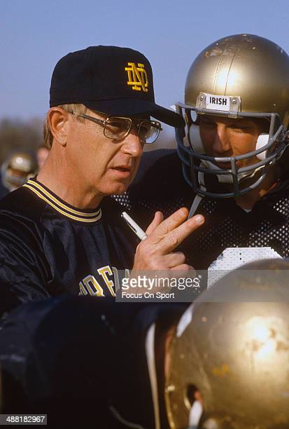 Head Coach Lou Holtz of the Notre Dame Fighting Irish give instructions to his players during a practice circa 1988 at Notre Dame in South Bend,...