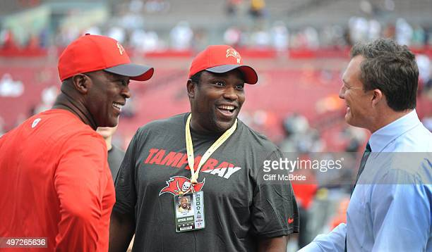 Head coach Lovie Smith of the Tampa Bay Buccaneers talks with former Buccaneers Warren Sapp and John Lynch during pregame at Raymond James Stadium on...