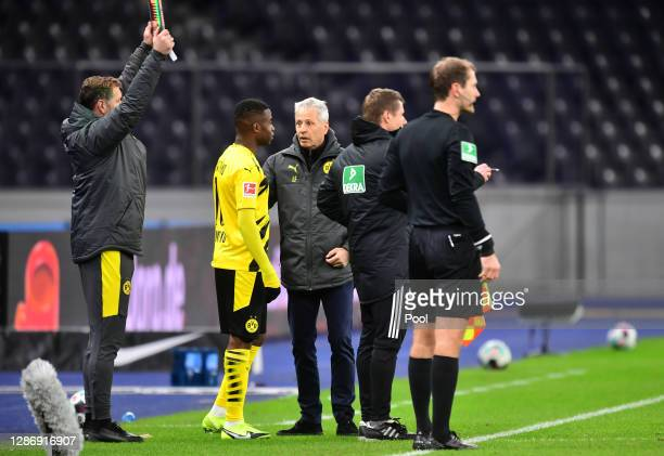 Head coach Lucien Favre of Dortmund talks to Youssoufa Moukoko before he replaces Erling Haaland during the Bundesliga match between Hertha BSC and...