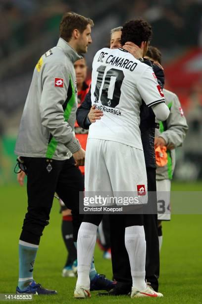 Head coach Lucien Favre of Moenchengladbach embraces matchwinnewr Igor de Camargo of Moenchengladbach after winning 21 the Bundesliga match between...