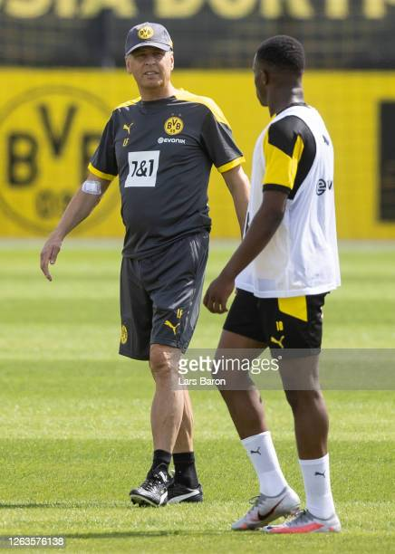 Head coach Lucien Favre speaks to Youssoufa Moukoko during the first training session of Borussia Dortmund after the summer break on August 03, 2020...