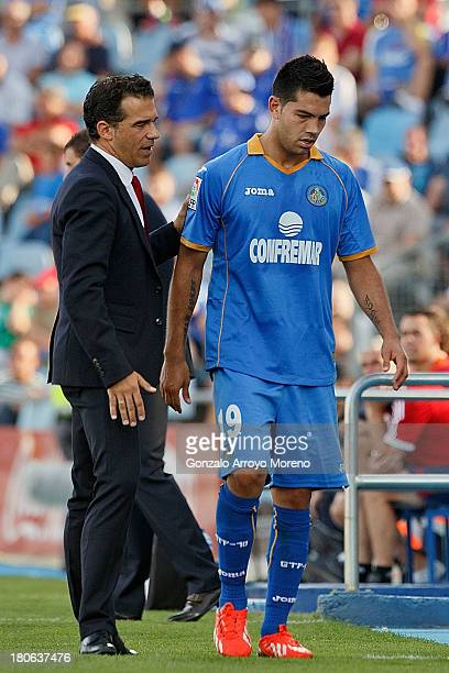 head coach Luis Garcia of Getafe CF greets his player Miku after being relevated during the La Liga match between Getafe CF and CA Osasuna at...