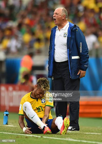 Head coach Luiz Felipe Scolari of Brazil reacts as Neymar sits on the field during the 2014 FIFA World Cup Brazil Group A match between Brazil and...