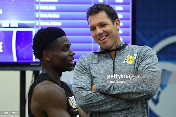 Head coach Luke Walton of the Los Angeles Lakers speaks with Aaron Holiday during Day One of the NBA Draft Combine at Quest MultiSport Complex on May...