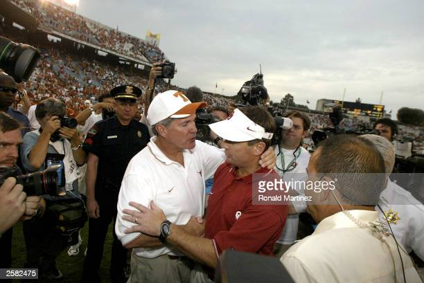Head coach Mack Brown of the Texas Longhorns and Bob Stoops of the Oklahoma Sooners greet each other at the end of the game at the Cotton Bowl on...