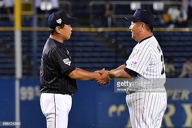 Head Coach Mamoru Koeda of U18 Japan and Head Coach Hiroki Yokoi of Collegiate Japan Shake hands during in the sendoff game between U18 Japan and...