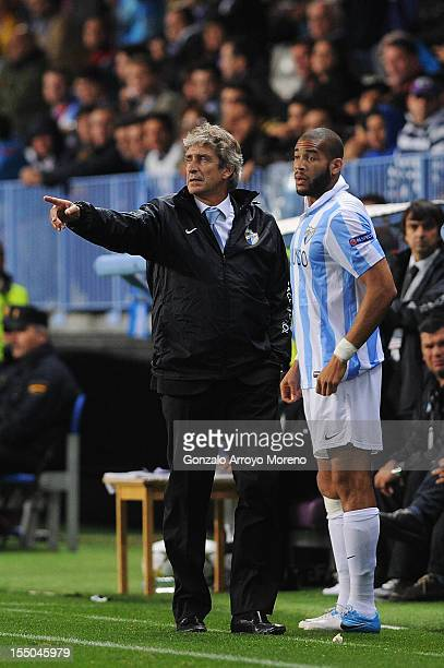 Head coach Manuel Pellegrini of Malaga CF gives instructions to player Oguchi Onyewu during the UEFA Champions League group C match between Malaga CF...