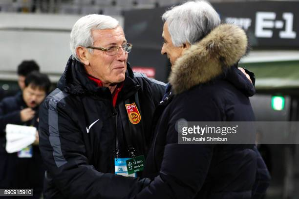 Head coach Marcello Lippi of China and Head coach Vahid Halilhodzic of Japan greet prior to the EAFF E1 Men's Football Championship match between...