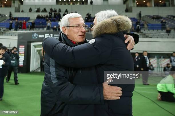Head coach Marcello Lippi of China hugs head coach Vahid Halilhodzic of Japan prior to the EAFF E1 Men's Football Championship between Japan and...