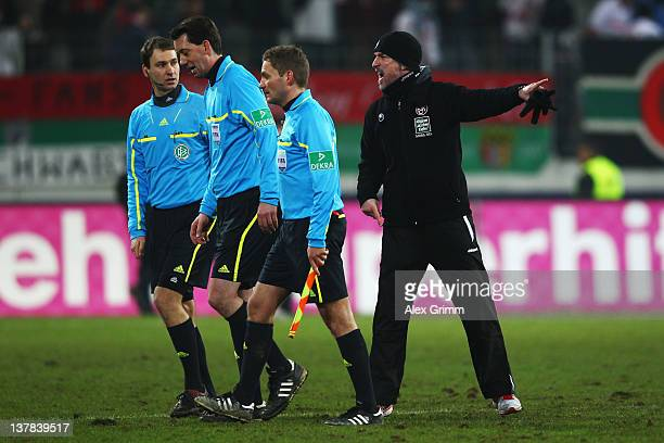 Head coach Marco Kurz of Kaiserslautern discusses with referee Manuel Graefe after the Bundesliga match between FC Augsburg and 1 FC Kaiserslautern...