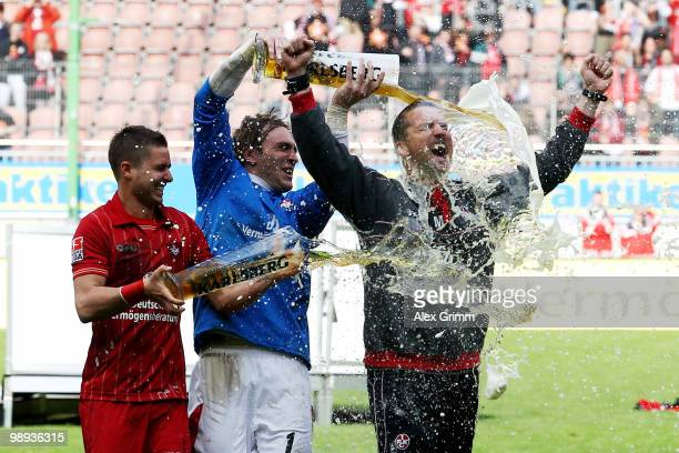 Head coach Marco Kurz of Kaiserslautern is showered with beer by goalkeeper Tobias Sippel and Markus Steinhoefer after the Second Bundesliga match...