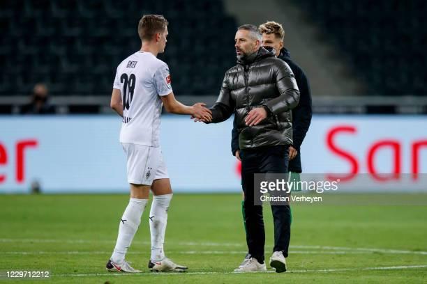 Head Coach Marco Rose of Borussia Moenchengladbach and Matthias Ginter of Borussia Moenchengladbach greet after the Bundesliga match between Borussia...