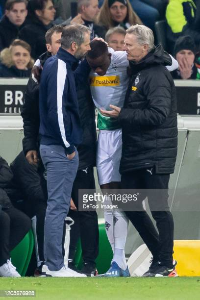 head coach Marco Rose of Borussia Moenchengladbach with Denis Zakaria of Borussia Moenchengladbach injured during the Bundesliga match between...
