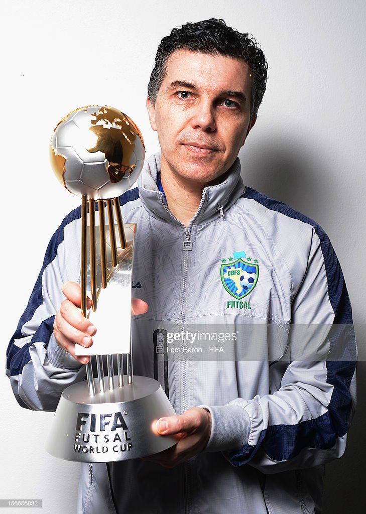 Head coach Marcos Sorato of Brazil poses with the trophy in the locker room after winning the FIFA Futsal World Cup Final at Indoor Stadium Huamark on November 18, 2012 in Bangkok, Thailand.
