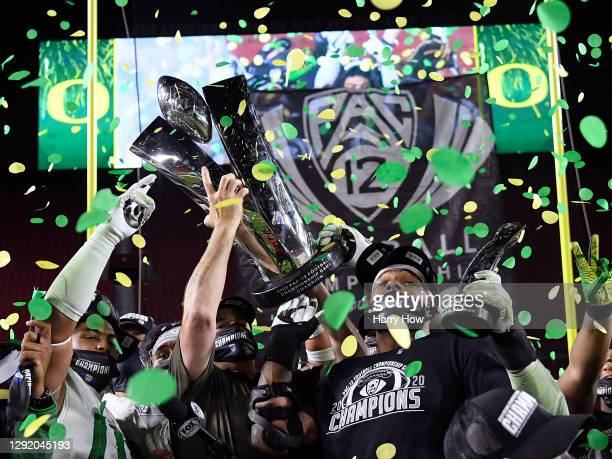 Head coach Mario Cristobal hoists the trophy, with most valuable player, Kayvon Thibodeaux of the Oregon Ducks, in celebration a 31-24 win over the...