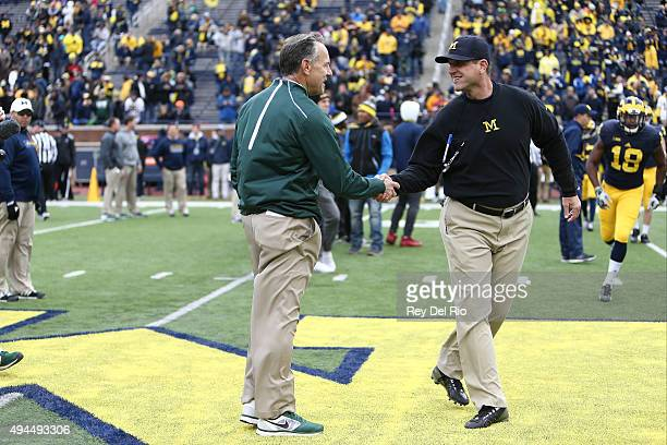 Head coach Mark Dantonio of the Michigan State Spartans and Head coach Jim Harbaugh of the Michigan Wolverines shake hands prior to the start of the...