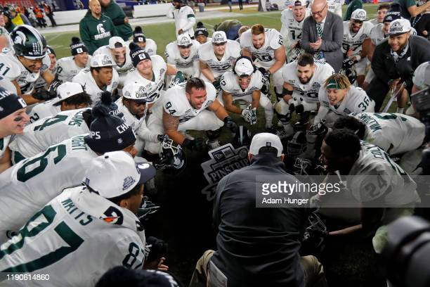 Head coach Mark Dantonio of the Michigan State Spartans celebrates with his players after defeating the Wake Forest Demon Deacons in the New Era...