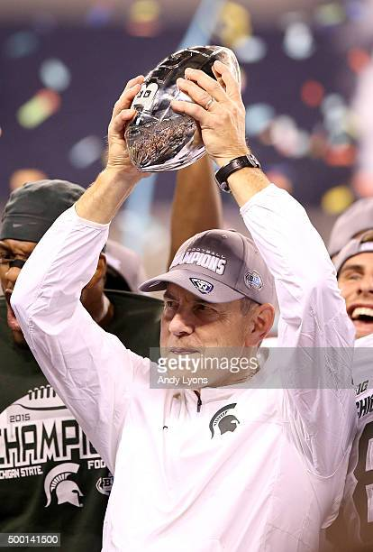 Head coach Mark Dantonio of the Michigan State Spartans hoists the trophy after beating the Iowa Hawkeyes in the Big Ten Championship at Lucas Oil...