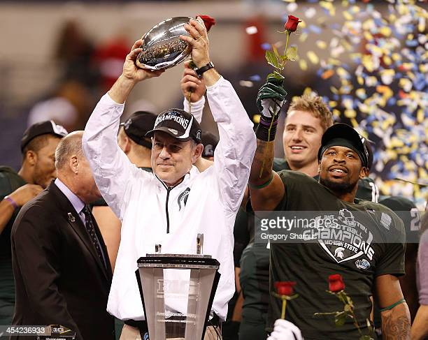 Head coach Mark Dantonio of the Michigan State Spartans holds up the Big Ten championship trophy next to Denicos Allen after defeating the Ohio State...
