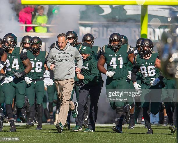 Head coach Mark Dantonio of the Michigan State Spartans leads his team onto the field before a college football game against the against the Rutgers...