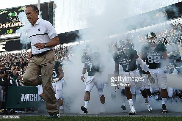 Head coach Mark Dantonio of the Michigan State Spartans takes the field with his team prior to a game against the Furman Paladins at Spartan Stadium...