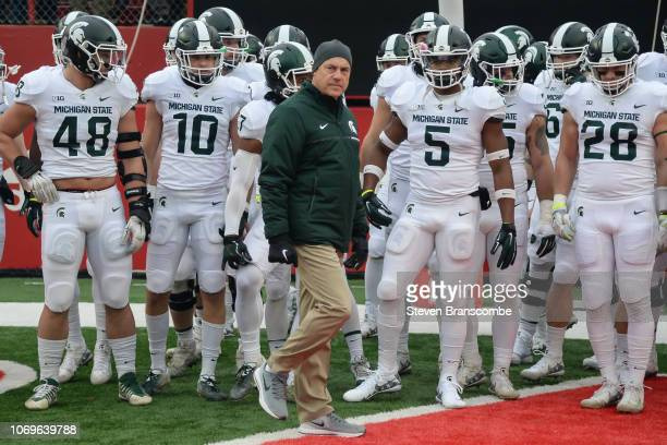 Head coach Mark Dantonio of the Michigan State Spartans walks on the field with the team before the game against the Nebraska Cornhuskers at Memorial...