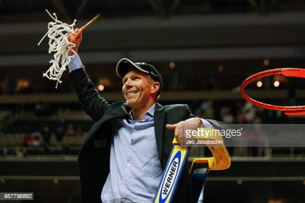 Head Coach Mark Few center of the Gonzaga Bulldogs celebrates a 8359 win as he cuts down the net over the Xavier University Musketeers as he cuts...