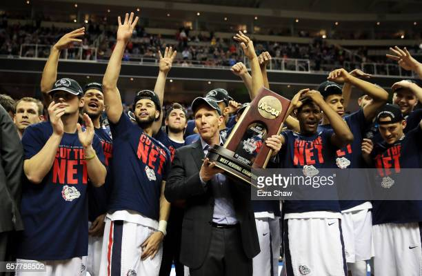 Head coach Mark Few of the Gonzaga Bulldogs and his team celebrate with the trophy after their 83 to 59 win over the Xavier Musketeers during the...