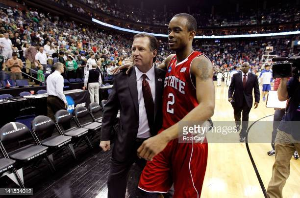 Head coach Mark Gottfried of the North Carolina State Wolfpack walks off the court with Lorenzo Brown after defeating the Georgetown Hoyas during the...
