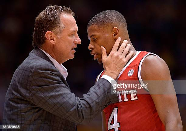 Head coach Mark Gottfried talks to Dennis Smith Jr #4 of the North Carolina State Wolfpack during their win against the Duke Blue Devils at Cameron...