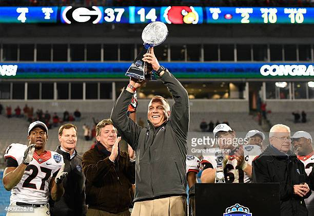 Head coach Mark Richt and the Georgia Bulldogs holds up the trophy after winning the Belk Bowl against the Louisville Cardinals at Bank of America...