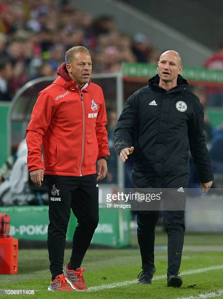 Head coach Markus Anfang of FC Koeln speaks with Fourth referee Daniel Riehl during the DFB Cup match between 1 FC Koeln and FC Schalke 04 at...