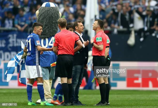 Head coach Markus Weinzierl of Schalke discusses with referee Felix Zwayer after the Bundesliga match between FC Schalke 04 and Borussia Dortmund at...