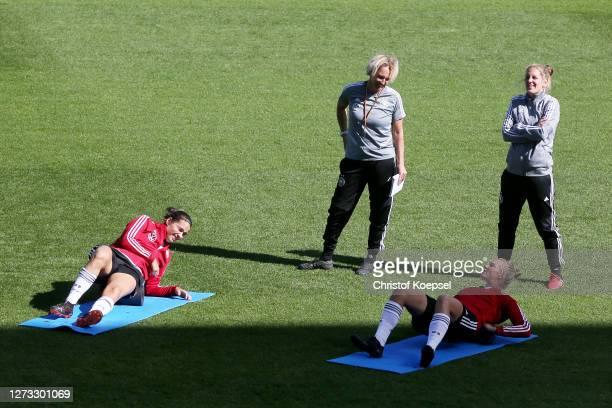 Head coach Martina VossTecklenburg and Britta Carlson assistant coachr watch Dzsenifer Marozsan and Alexandra Popp during a Germany Women's training...