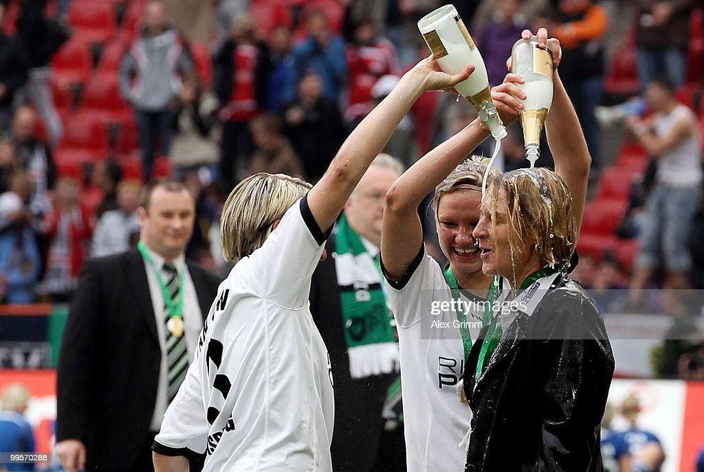 Head coach Martina Voss-Tecklenburg of Duisburg is showered with champaign by Alexandra Popp and Anne van Bonn (R-L) after winning the DFB Women's Cup final match between FCR 2001 Duisburg and FF USV Jena at RheinEnergie stadium on May 15, 2010 in Cologne, Germany.