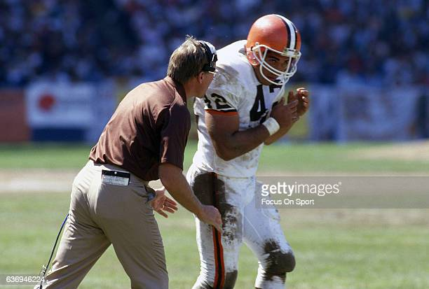 Head Coach Marty Schottenheimer of the Cleveland Browns talks with his player Tim Manoa during an NFL football game circa 1987 at Cleveland Municipal...