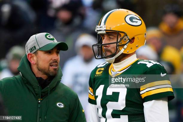 head coach Matt LaFleur of the Green Bay Packers discusses with Aaron Rodgers of the Green Bay Packers during warms up before the game against the...